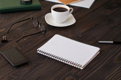 Office desk with a notebook with blank pages and coffee Royalty Free Stock Photo