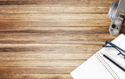 Office desk with notebook on brown wood background Stock Photo