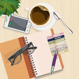 Office desk with notebook, eyeglasses, coffee and laptop. Stock Images