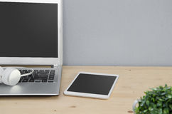 Office Desk with notebook, tablet and earphone. Stock Photo