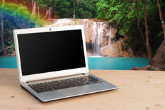 Office Desk with Notebook and Water fall Background. View from front with notebook space Royalty Free Stock Photos