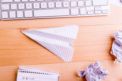 Office Desk, Paper Airplane. Studio Shot, Wooden Background. Stock Photos