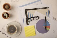 Office desk with paperwork and statistics. Top view of busy office desk filled with graphs royalty free stock images