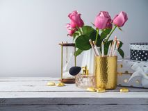 Office desk with pencils, roses and perfume bottle Royalty Free Stock Images