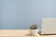 Office Desk with pink rose on flower pot and back monitor laptop. Royalty Free Stock Photo