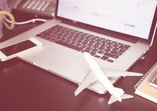 Office desk with plane and laptop for business travel. Concept Stock Photo