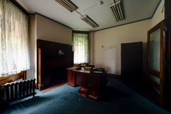 Office with Desk, Religious Books and Bust - Abandoned Church Rectory. A view inside an office with a desk, some books and a bust in an abandoned church rectory Royalty Free Stock Image