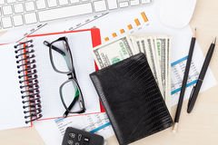 Office desk with reports, blank notepad and money cash Royalty Free Stock Photography
