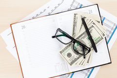 Office desk with reports, blank notepad and money cash Stock Images