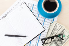 Office desk with reports, blank notepad and money cash Royalty Free Stock Images