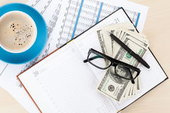 Office desk with reports, blank notepad and money cash Royalty Free Stock Photo