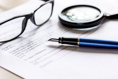 Office desk with signing contract, glasses, magnifier and pen for business Royalty Free Stock Photos