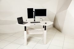 Office desk for sitting and standing. An office table with two manitors, a lifting mechanism for the holder of the manitor and a tabletop behind which you can stock image
