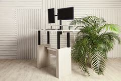 Office desk for sitting and standing. An office table with two manitors, a lifting mechanism for the holder of the manitor and a tabletop behind which you can stock photo