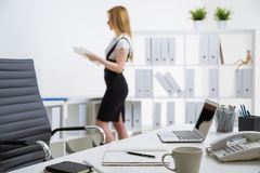 Office desk and standing businesswoman. Closeup of desktop with various items and office tools and standing businesswoman with document in the background Royalty Free Stock Photos
