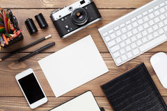 Office desk with supplies, camera and blank card Royalty Free Stock Photo