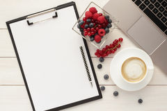 Office desk table with clipboard, coffee cup and healthy food. Home office desk table with clipboard, blank paper, computer, healthy snack - berries in a bowl Royalty Free Stock Images