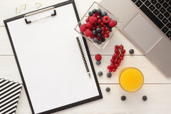 Office desk table with clipboard and healthy food. Home office desk table with clipboard, blank paper, computer, healthy snack - fresh berries in a bowl  and Stock Photo