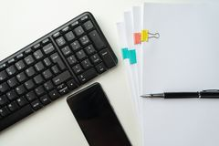 Office desk table with computer keyboard and supplies. On white background. Top view with copy space. Mock up. Office desk table with computer keyboard and royalty free stock photo