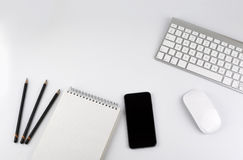 Office desk table with computer, Smartphone, note pad, pencils - Royalty Free Stock Images