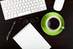 Office desk table with computer, supplies, coffee and glasses Royalty Free Stock Photography