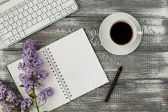 Office desk table with computer, supplies, cup of coffee and peony flowers. White wooden background. Coffee break, ideas, notes, g Stock Photography
