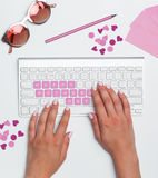 Office desk table with female hands, computer, supplies, flowers Royalty Free Stock Images