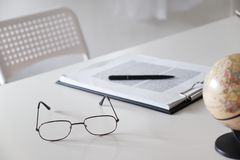 Office desk table with glasses, pen, pencil and world map royalty free stock image