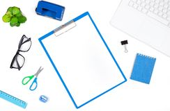 Office desk table with Laptop, Notebook, Hole Puncher, Clipboard. Office desk table with Laptop, Blue Notebook, Hole Puncher, Clipboard, Cup of Coffee and Flower Stock Photography