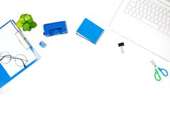 Office desk table with Laptop, Notebook, Hole Puncher, Clipboard. Cup of Coffee and Flower. Top view with copy space Stock Photos