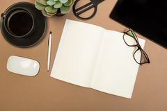 Office desk table with  notebook scissors glasses coffee cup succulent and pencil. Mock up template . Top view stock photography