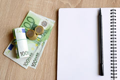 Office desk table with pen,notebook and money. Stock Photography