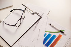 Office desk table with pen, papers, graphics and glasses. Top view with copy space selective focus Royalty Free Stock Photo