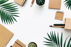 Office desk table with stationery set, supplies and palm leaves. royalty free stock images