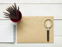 Office desk table with supplies. Magnifying glass, pencil and empty blank sheet of paper. Top view. Copy space for text Stock Image