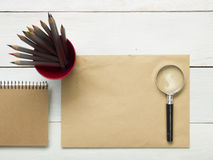 Office desk table with supplies. Magnifying glass, pencil and empty blank sheet of paper. Top view. Copy space for text Royalty Free Stock Photo