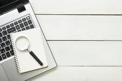 Office desk table with supplies. Top view. Copy space for text. Laptop, blank notepad, and magnifying glass Stock Photo