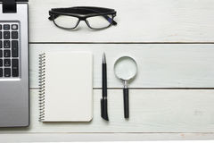 Office desk table with supplies. Top view. Copy space for text. Laptop, blank notepad, pen and magnifying glass Royalty Free Stock Image