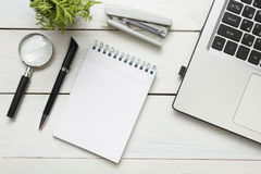Office desk table with supplies. Top view. Copy space for text. Laptop, blank notepad, pen, magnifying glass, calculator Royalty Free Stock Photo