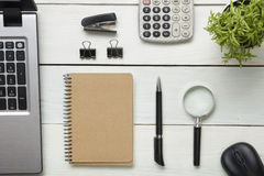 Office desk table with supplies. Top view. Copy space for text. Laptop, blank notepad, pen, magnifying glass, calculator Stock Image