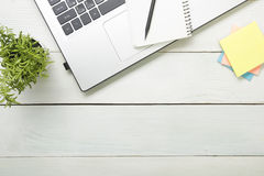Office desk table with supplies. Top view. Copy space for text. Laptop, notepad, pen and flower. Stock Photos