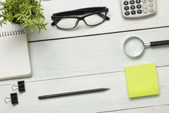 Office desk table with supplies. Top view. Copy space for text. Notepad, pen, glasses, calculator, reminder, flower. Royalty Free Stock Photo