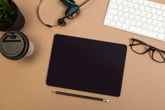 Office desk table with  tablet  keyboard headphones coffee and glasses Mock up template . Top view stock photo