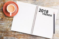 Text 2018 TRENDS on blank paper notebook. Office desk table-Text 2018 TRENDS on blank paper notebook with pencil and cup of coffee on wooden table.View from Royalty Free Stock Photography