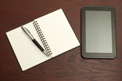 Office desk with a tablet, notebook and a pen Stock Image