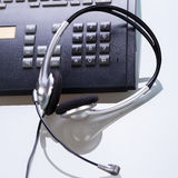Office desk with telephone and headset objects Stock Photos