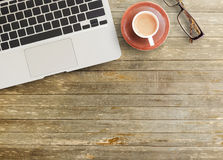 Office desk - Top view of brown wooden office table. With cup of coffee,glasses,pencil and notepad. working office space. objects on the table. office working Royalty Free Stock Photo
