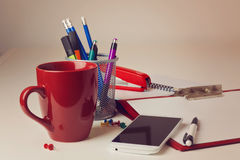 Office desk with various items including coffee cup and smart phone over blur background Royalty Free Stock Images