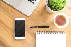 Office desk wooden table with smart phone, cup of tea, laptop, pen, plant and notebook.Top view with copy space.Work at home and o. Ffice concept royalty free stock photo