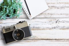 Office desk wooden table with vintage camera and fresh flower. Office desk wooden table with vintage camera,notebook,pencil and fresh flower. Top view with copy Stock Photos